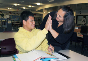 Student and teacher celebrate with a high five
