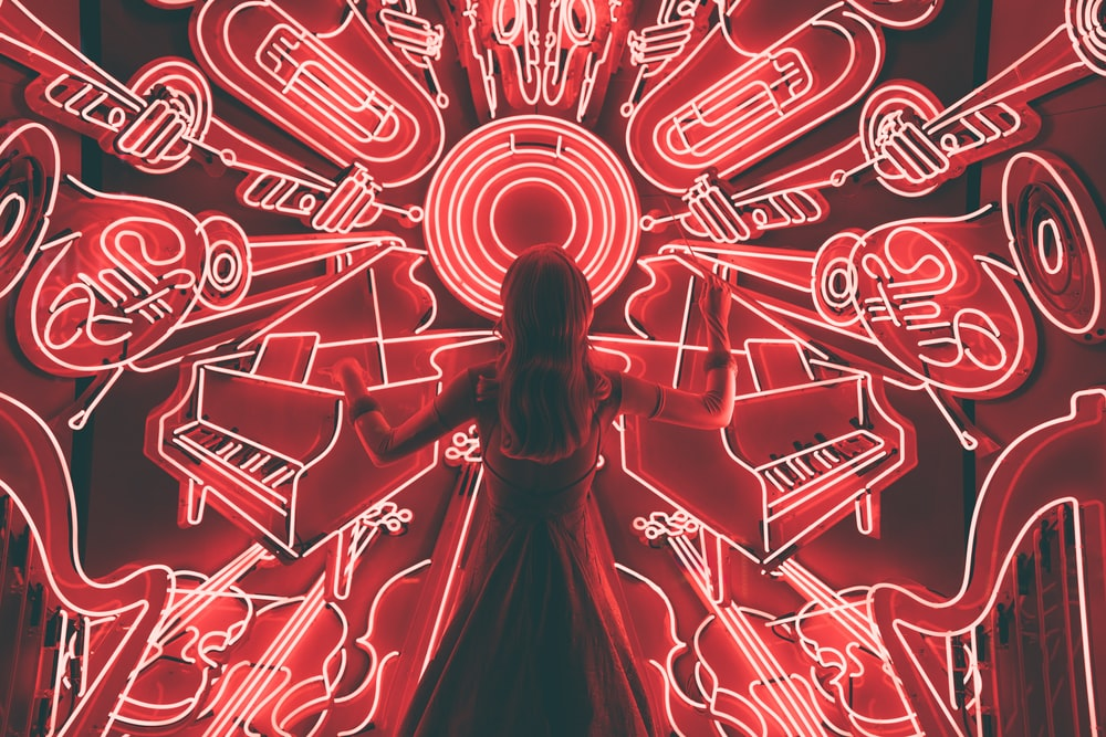 Person standing in front of neon lights in the shape of instruments